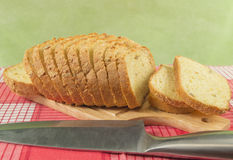 Sliced wheat bread on cutting Board closeup. Knife, red napkin Stock Images
