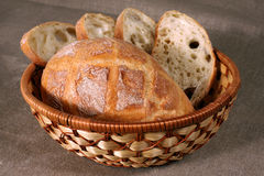 Sliced white bread is in a straw basket on the tablecloth gray l Stock Photos