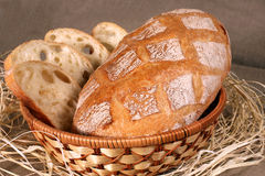 Sliced white bread is in a straw basket on the tablecloth gray l Royalty Free Stock Photography