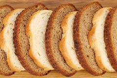 Sliced white and brown loaf of bread. Royalty Free Stock Images