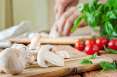 Sliced white button mushrooms on a cutting board with basil Stock Image