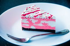 Sliced White and Pink Icing Covered Cake on White Plate With Silver-colored Fork royalty free stock photo