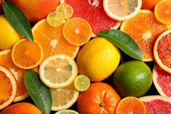Sliced and whole citrus fruits with leaves as background. Top view stock images