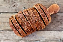 Sliced whole grain bread with flax, above view on wood Stock Images