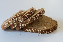 Sliced whole grain bread with oat flakes. Sliced healthy wholegrain bread with some oat flakes on the edge, on white background Royalty Free Stock Images
