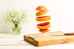 Sliced whole grapefruit flying above a wooden chopping board Stock Photo