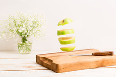 Sliced whole green apple flying above a wooden chopping board. With a knife Royalty Free Stock Images