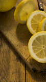 Sliced and whole lemons o wooden chopping board an table Royalty Free Stock Image
