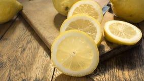 Sliced and whole lemons o wooden chopping board an table. Sliced and whole lemons on wooden chopping board and table. High resolution image Stock Photo