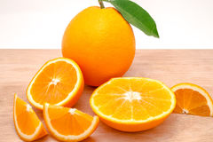 Sliced and whole oranges on a board, isolated on white background Royalty Free Stock Photos