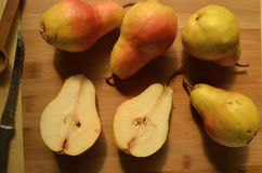 Sliced and whole pears on cutting board overhead view Stock Images