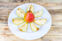 Sliced and whole pears in white plate, rustic wooden table Stock Photo