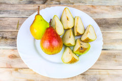 Sliced and whole pears in white plate, rustic wooden table Royalty Free Stock Photo
