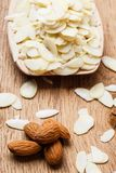 Sliced and whole raw almonds on wooden surface Stock Photos
