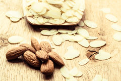 Sliced and whole raw almonds on wooden surface Royalty Free Stock Image