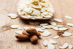 Sliced and whole raw almonds on wooden surface Royalty Free Stock Photos
