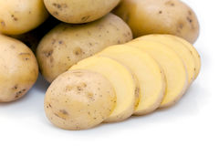 Sliced and whole raw potatoes Royalty Free Stock Images