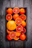 Sliced and whole ripe juicy blood oranges and grapefruit in the box on wooden background. Stock Photo