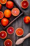Sliced and whole ripe juicy blood oranges and grapefruit in the box on wooden background. Royalty Free Stock Images