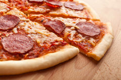 Sliced whole salami pizza on wooden table Stock Image
