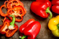 Sliced and whole sweet pepper. On wooden background stock photos
