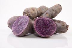 Sliced and whole Vitelotte potatoes Royalty Free Stock Photos