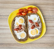 Sliced whole wheat bread with butter, tuna, sausage, cherry toma Stock Image