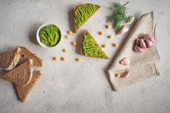 Sliced whole wheat bread with guacamole, chickpea and garlic on the grey concrete backdrop. royalty free stock photography