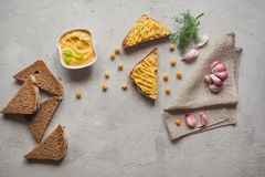 Sliced whole wheat bread with hummus, chickpea and garlic on the grey concrete backdrop. royalty free stock photo