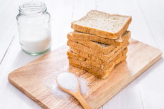 Sliced whole wheat bread with sugar on white wooden table.  Stock Photo