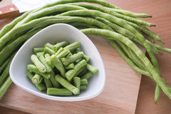 Sliced yard long bean vegetable on the white dish and wooden block. Royalty Free Stock Image