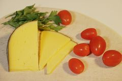Sliced yellow cheese and small red tomatoes stock images