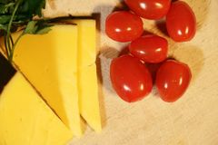 Sliced yellow cheese and small red tomatoes royalty free stock photo