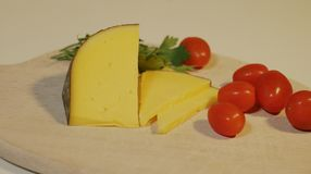 Sliced yellow cheese and small red tomatoes royalty free stock photography