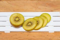 Sliced yellow kiwi on on wood background. Stock Images