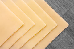 Sliced yellow sandwich cheese. Neatly arranged on a wood surface. Shot from above Royalty Free Stock Images
