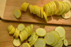 Sliced yellow squash on cutting board on outdoor picnic table. Under shade tree --squash sliced in preparation for grilling Royalty Free Stock Photo