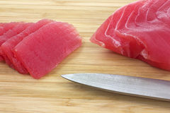 Sliced yellowfin tuna on cutting board Royalty Free Stock Image