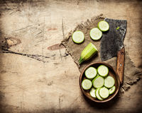 Sliced zucchini and an old hatchet . Stock Photos