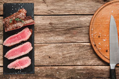 Slices of appetizing and juicy medium-rare steak. Delicious grilled beef steak sliced on black slate with professional knife on platter on rustic wooden table Royalty Free Stock Images