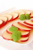Slices of apple. With mint leaves on a white plate Royalty Free Stock Images