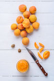 Slices of apricots, fresh apricots and apricot puree in glass ja. Apricot puree in a glass jar, knife, slices of fresh apricot and apricot seeds on a white stock photos
