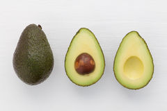 Slices of avocado on white background. Whole and half with core. Stock Images