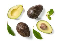 Slices of avocado on white background. Whole and half with leaves. Design element for product label. Top view royalty free stock photography
