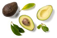 Slices of avocado on white background. Whole and half with leaves. Design element for product label. Top view royalty free stock images