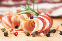 Slices of bacon. Slices of rolled bacon with rosemary and peppercorn Royalty Free Stock Photo