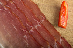 Slices of bacon. Some slices of bacon on wooden background Royalty Free Stock Photo