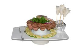 Slices of baked beef with onion, parsley, lime and spicy sauce, decorated with radish flowers. Stock Photo