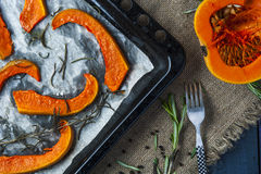 Slices of baked pumpkin on baking tray with fork Royalty Free Stock Photos
