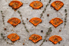 Slices of baked pumpkin with spices and herbs. Flat lay. Closeup of prepared spiced squash on cooking parchment. Seasonal , healthy food, vegetarian menu , real Stock Photo